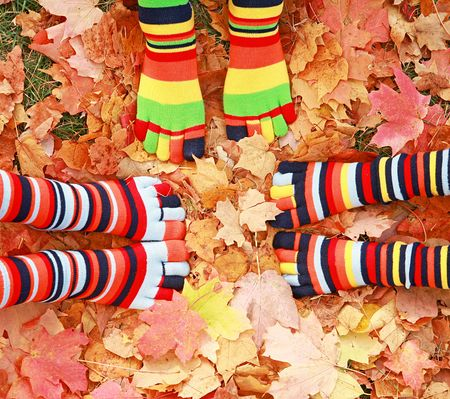 children at play: Three Childrens Feet in Autumn Leaves
