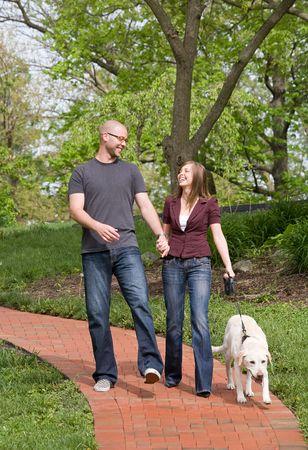 그들의 개를 산책하는 행복 한 젊은 커플