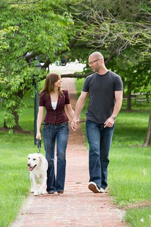 smile close up: Happy Young Couple Walking the Dog Stock Photo