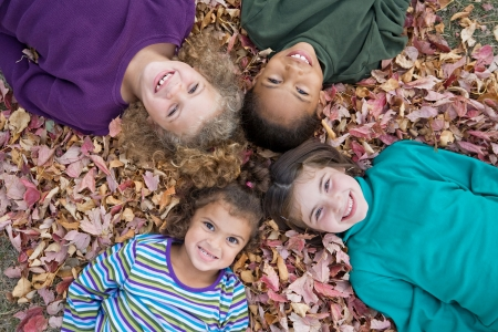 lying in leaves: Four Girls Playing in Fall Leaves Stock Photo