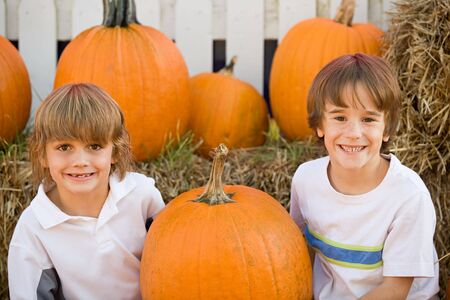 Two Boys Smiling in a Pumpkin Patch photo