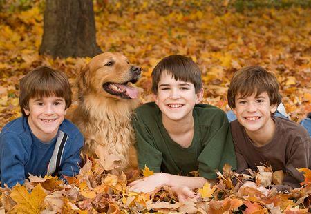 가을 잎에 강아지와 누워 소년 스톡 콘텐츠
