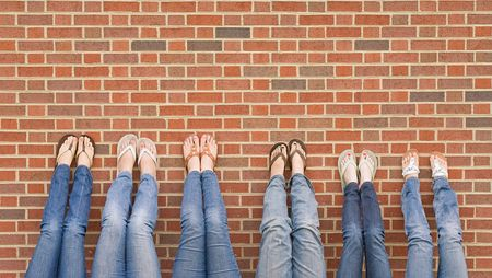 Group of College Girls at School With Legs up on Wall Foto de archivo