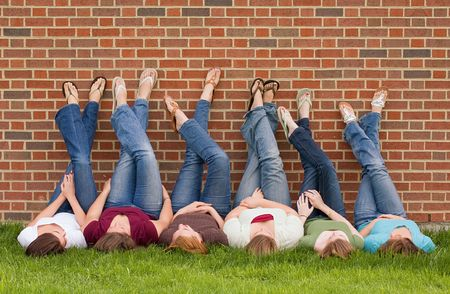 school friends: Group of College Girls at School With Legs up on Wall Stock Photo
