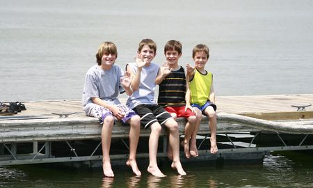 Boys Waving Sitting on the Dock Banco de Imagens