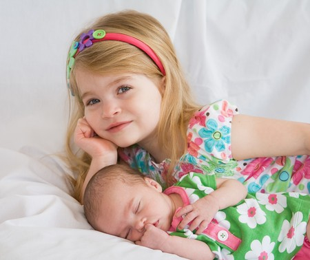 Sister Laying with New Baby Sister Foto de archivo