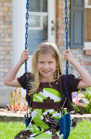 Little Girl Swinging in Front of Her House Banco de Imagens