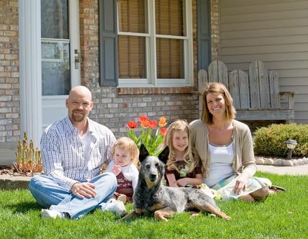 Familie voor hun huis zit Stockfoto
