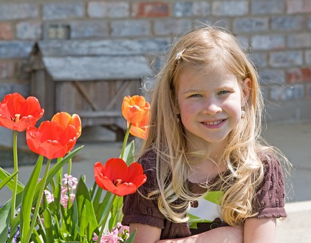 Little Girl Sitting in Front of Home with Tulips