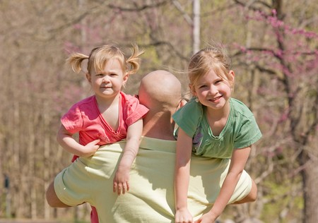 Dad Carrying His Daughters  Standard-Bild - 7447808