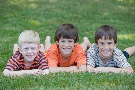 Three Cousins Laying in a Row Smiling Big
