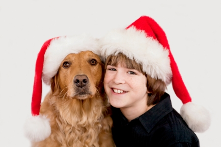 Boy and Dog Wearing Christmas Hats photo