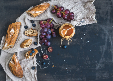 French baguette cut into pieces, red grapes, blueberry and salty caramel sauce on linen towel over rustic dark background with a copy space. Top view photo