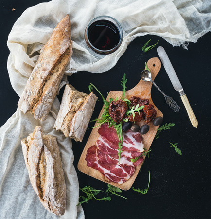 Wine and appetizer set: a glass of red wine, vintage dinnerware, white kitchen towel french baguette broken into pieces, dried tomatoes, olives, smoked meat and arugula on a rustic wooden board over a dark background. Top view Фото со стока