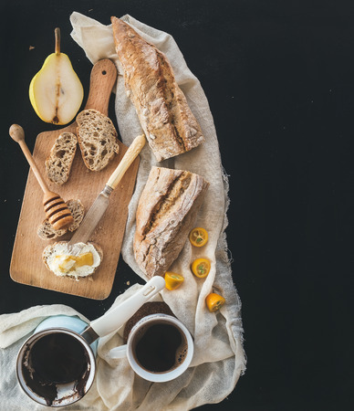 black bread: Breakfast set: a pot (cezve) of coffee, a cup on a kitchen towel, kumquats, pears, baguette slices with butter cream and honey on a rustic wooden board over a black backdrop with a copy space. Top view