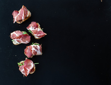 Bruschettas with dried tomatoes, arugula and smoked meat over a black backdrop with a copy space. Top view