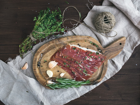 Cured pork meat or prosciutto on a rustic woodem board with garlic, spices and thyme over a piece of linen fabric and dark wood background. Top view photo