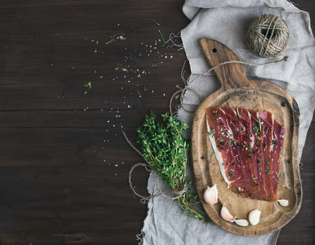 Cured pork meat prosciutto on a rustic woodem board with garlic, spices and thyme over a piece of linen fabric and dark wood background with a copy space. Top view photo