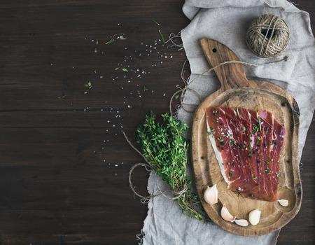 Genezen varkensvlees prosciutto op een rustieke woodem bord met knoflook, kruiden en tijm over een stuk linnen doek en donker hout achtergrond met een kopie ruimte. bovenaanzicht
