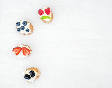 berry fruit: Sweet berry (strawberry, raspberry, blueberry and blackberry) and soft cheese sandwiches (bruschattas) over a white wooden background with a copy space. Top view Stock Photo