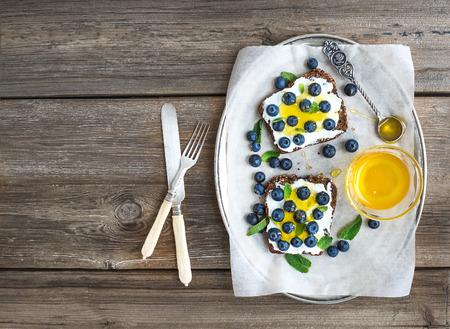 bocadillo: Juego de desayuno saludable con ricotta, arándanos frescos y sándwiches de miel en el pan de grano entero servido con menta en un plato de plata sobre un fondo de madera rústica con un espacio de copia. Vista superior