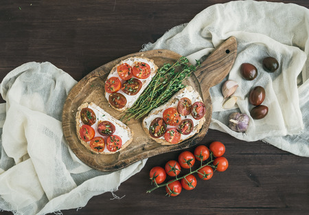 Sandwiches or brushettas with roasted cherry tomatoes, soft cheese, garlic and herbs on a rustic wooden board and white kitchen towel over a dark wood background. Top view photo