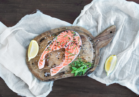Raw salmon steak with fresh herbs, lemon and spices on rustic wooden board and white linen towel over a dark wood background. Top view photo