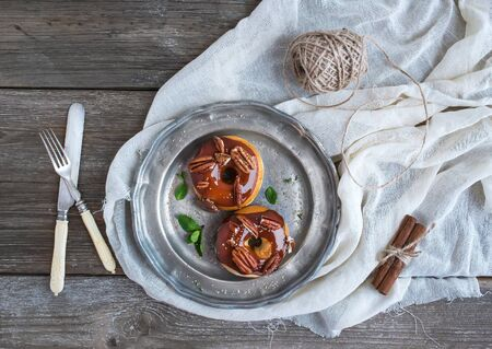 pekan: Cinnamon donuts with caramel icing and pekans served with fresh mint and cane sugar on a vintage metal plate over a white table cloth over a rustic wood background. Top view