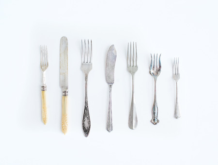 A set of vintage dinnerware: knifes and forks of different shapes and sizes on a white background. Top view Stock Photo
