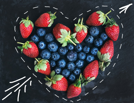 Saint Valentine's day greeting berry set. Fresh garden straberries and blueberries places together in a shape of heart over a rough black stone background. Top view