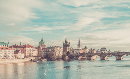stare mesto: The view over the Vltava river, Charles bridge and white swans from Mala Strana in Prague, Czech Republic, on a clear sunny winter day Stock Photo
