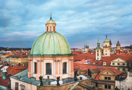 The view over the dome of Saint Francis of Assisi church and red roofs of Stare Mesto district in Prague, Czech Republic, from the view point on top of the tower of the Charles bridge on a cloudy winter evening