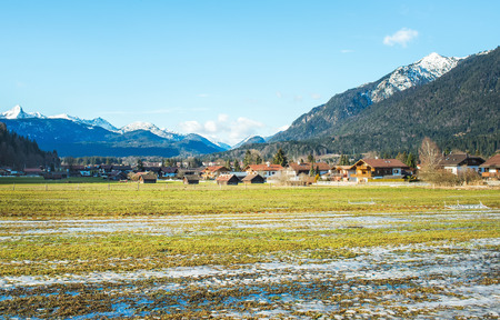 winter thaw: The green valley in Bavarian Alps near Garmisch-Partenkirchen town during a thaw in winter season on a sunny clear day