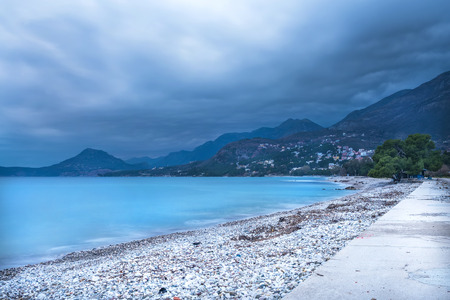 nasty: The landscape of the Adriatic coast of Bar, Montenegro before the storm: nasty dramatic sky, calm sea and misty mountains at the backdrop