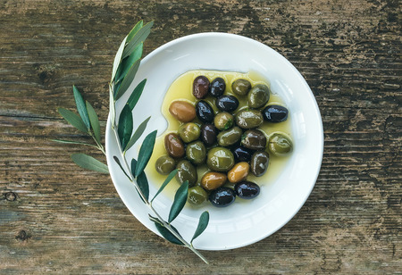 A plate of Mediterranean olives in olive oil with a branch of olive tree over a rough old wooden desk. Top view photo