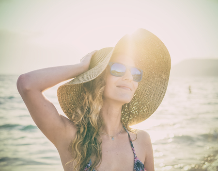 blondy: Young blondy girl in sunglasses and straw hat at the beach enjoying the sun