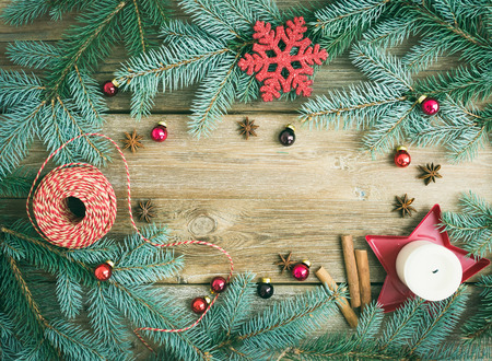 Christmas decorations: fur-tree branches, colorful glass balls, a candle, red glittering snowflacke, cinnamon sticks and anise stars on a rough wooden background with a copy space photo