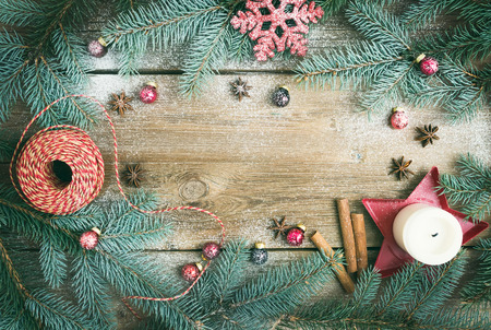 Kerstversiering: bont-boom takken, kleurrijke glazen ballen, een kaars, rood glinsterende snowflacke, kaneel en anijs sterren op een ruwe houten achtergrond met een kopie ruimte