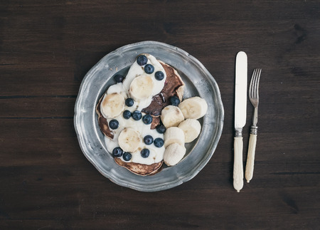 Breakfast set on dark wooden desk: apple and cinnamon pancakes with yogurt, banana, blueberry and maple syrup in a rustic metal plate. Top view photo