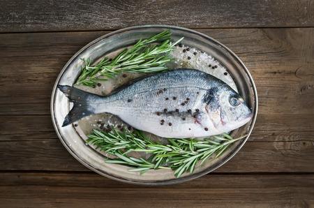 Le poisson frais de la mer (daurade) sur un plat en métal avec le romarin et épices prêt pour la cuisson sur un fond de bois rustique