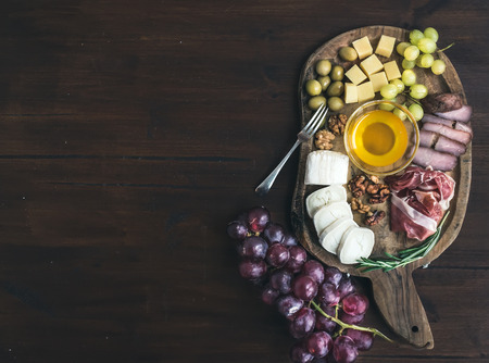wine and food: Wine appetizers set: meat and cheese selection, honey, grapes, walnuts and olives on a rustic wooden board over a dark wood backgroung with a copy space. Top view