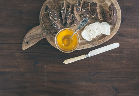 cope: Breakfast set on a dark wood background: fresh dark baguette cut in slices, goat brie cheese and honey on a rustic wooden board with a cope space
