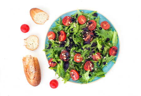 baguet: Vegetable salad with cherry-tomatoes and bread on a white surface