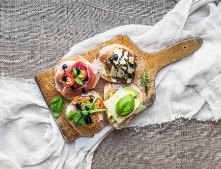 parmezan: Brusquetta set on a rustic wooden board over a piece of white linen fabric and a sackcloth background Stock Photo