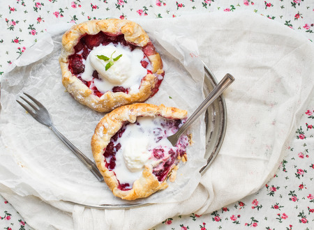 galettes: Small rustic berry galettes with ice-cream on a silver dish over a floral patterned table cloth Stock Photo