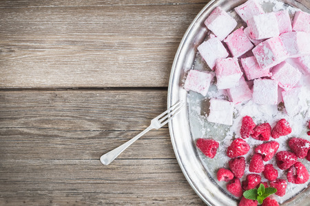 cope: Homemade raspberry marshmallow with fresh raspberries and sugar powder on a silver dish over a rustic wood background with a cope space