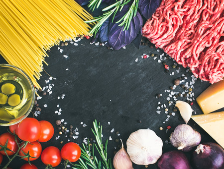 Spaghetti Bolognese ingredients: spaghetti pasta, minced meat, tomatoes, basil, rosemary, parmesan cheese, olive oil, garlic, onon, sea salt and spices on a dark stone background with a copy space in the center Banco de Imagens