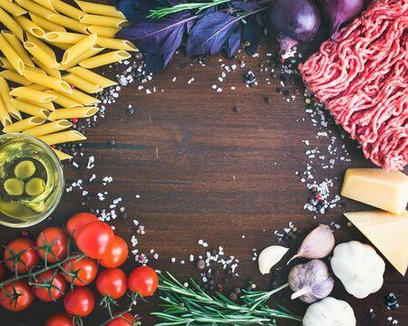 aceite de cocina: Ingredientes: pasta bolo�esa penne, carne picada, tomates, albahaca, romero, queso parmesano, aceite de oliva, ajo, onon, sal marina y especias sobre un fondo de piedra oscura con un espacio de copia en el centro