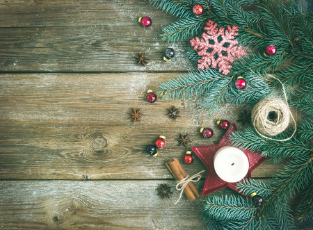 Christmas decorations: fur-tree branches, colorful glass balls, a candle, red glittering snowflacke, cinnamon sticks and anise stars on a rough wooden background with a copy space Stock Photo