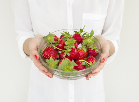 bawl: A bowl of strawberries in the hands of a woman in a white shirt
